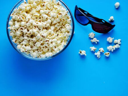 Popcorn for watching a movie in a Cup with 3D glasses on a blue background.