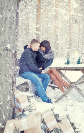 A couple in love embraces in a snow-covered forest , at a table set in a rustic style by candlelight