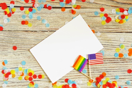 Bright rainbow gay flag on wooden background, paper confetti top view with space for text, mocup, copy space. LGBT community. acceptance symbol