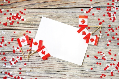 The national holiday of July 1- happy Canada day , Dominion day, the concept of patriotism, independence and memory, a place for text. white red confetti and mini flags on a wooden table