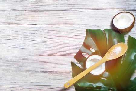 coconuts and leaf of tropical monstera plant with coconut flakes on wooden spoon on white wooden background. Flat layer, top view, copy space. Healthy cooking. Creative concept of healthy food and ecology. horizontal