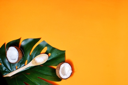 coconuts and leaf of tropical monstera plant with coconut flakes on orahge background. Flat layer, top view, copy space. Healthy cooking. Creative concept of healthy food and ecology. Stock fotó