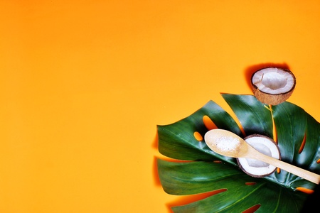 coconuts and leaf of tropical monstera plant with coconut flakes on orahge background. Flat layer, top view, copy space. Healthy cooking. Creative concept of healthy food and ecology. Banque d'images