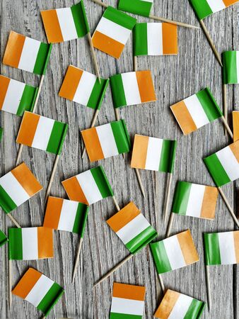 MARCH 17 Concept independence day of Ireland and Ireland national day. mini flags on white wooden background. vertical.