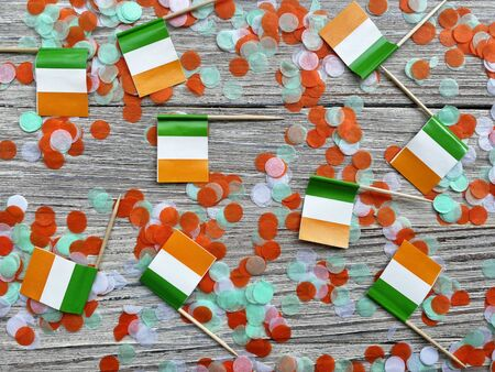 MARCH 17 Concept independence day of Ireland and Ireland national day. mini flags on white wooden background with confetti. horizontal
