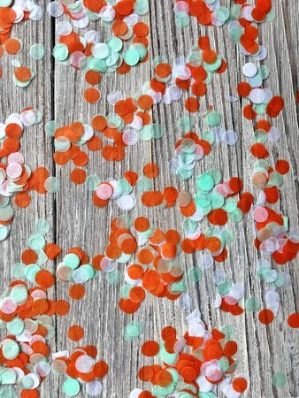 Three-color paper confetti on a white wooden background. Irish, india and Cinu, independence day concept. patriotism and freedom, the joy of the national holiday