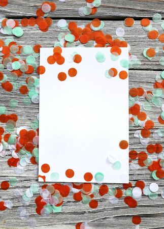 Tricolor paper confetti on a white wooden background. Irish, India and Chinu, independence day concept. patriotism and freedom, the joy of a national holiday. Mocup. copy space. space fo text. vertical
