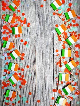 MARCH 17 Concept independence day of Ireland and Ireland national day.space for your text . mocup.mini flags with paper confetti lie on the edge of a white wooden background. vertical