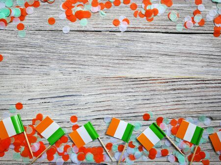 MARCH 17 Concept independence day of Ireland and Ireland national day.space for your text . mini flags on white wooden background with confetti, horizontal