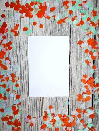 Tricolor paper confetti with a sheet of white paper on a white wooden background. Irish, India and Chinu, independence day concept. patriotism and freedom, the joy of a national holiday. Mocup. copy space. space fo text.