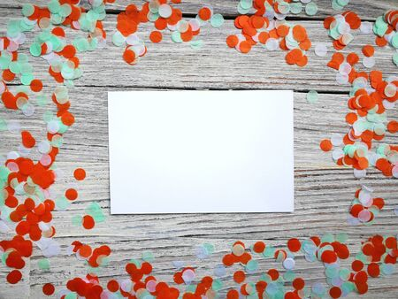 Tricolor paper confetti with a sheet of white paper on a white wooden background. Irish, india and Cinu, independence day concept. patriotism and freedom, the joy of the national holiday. mocup, copy space. horizontal