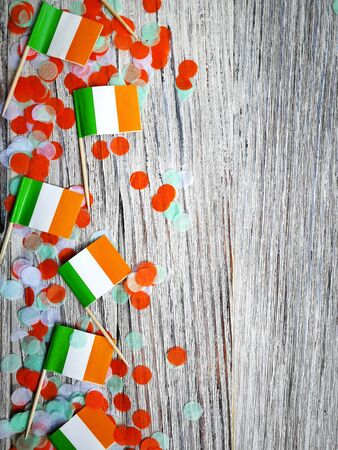 MARCH 17 Concept independence day of Ireland and Ireland national day.space for your text,mini flags with paper confetti lie on the edge of a white wooden background, vertical Stockfoto