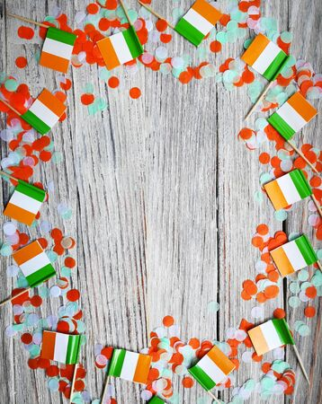 MARCH 17 Concept independence day of Ireland and Ireland national day.space for your text . mini flags on white wooden background with confetti. vertical.