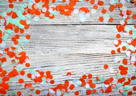 Three-color paper confetti on a white wooden background.