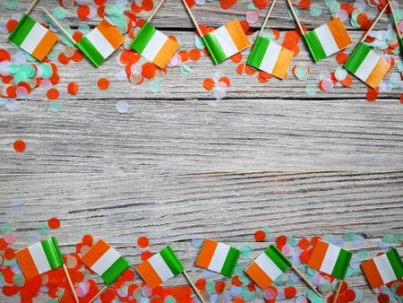MARCH 17 Concept independence day of Ireland and Ireland national day.space for your text . mini flags with paper confetti lie on the edge of a white wooden background. horizontal Stockfoto
