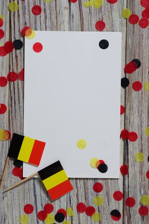 Flag of Belgium hanging on clothesline attached with wooden clothespins on white wooden background. National day concept.