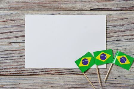 September 7. Independence day of Brazil, the concept of independence , patriotism and freedom. Mini paper flags with confetti and white postcard on wooden background