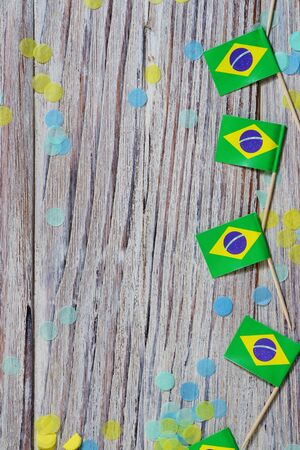 September 7. Brazil independence day concept of independence , patriotism and freedom. Mini paper flags with confetti on wooden background. vertical