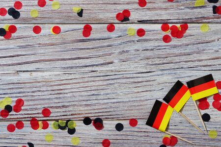 Day of German Unity written in German, and some flags of Germany against a rustic wooden background