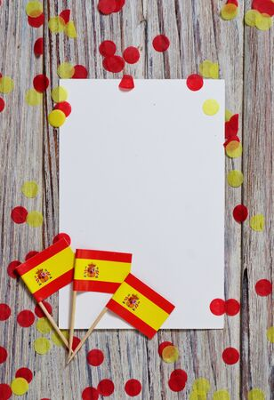 Independence Day of Spain concept with flag in hand on white wooden background top view