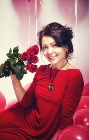 Full length portrait of a happy young woman dressed in red dress holding bouquet of roses while standing and celebrating over white background. Banco de Imagens