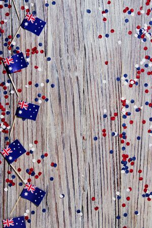 Australia independence day. 26 Jan . the concept of patriotism, freedom and independence. mini flags with red white blue and confetti white card on wooden background Banco de Imagens - 128259196