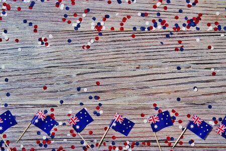 Australia independence day. 26 Jan . the concept of patriotism, freedom and independence. mini flags with red white blue and confetti white card on wooden background Banco de Imagens - 128259197