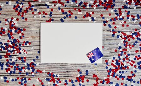 Australia independence day. 26 Jan . the concept of patriotism, freedom and independence. mini flags with red white blue and confetti white card on wooden background