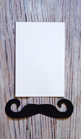 white paper envelop on old wooden table with vintage tone. black paper mustache. Happy father's day - words. Banco de Imagens - 128259255