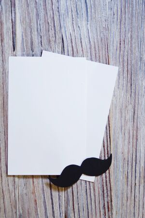 white paper envelop on old wooden table with vintage tone. black paper mustache. Happy fathers day - words.