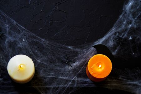 Halloween decoration with spider on web, and candles on black background. Banco de Imagens