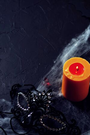 Halloween. a black female mask lies next to a burning candle on a web with spiders and bats on a black background. Banco de Imagens - 128259334