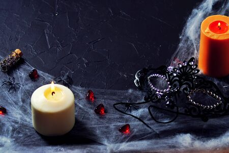 Halloween. a black female mask lies next to a burning candle on a web with spiders and bats on a black background. Banco de Imagens