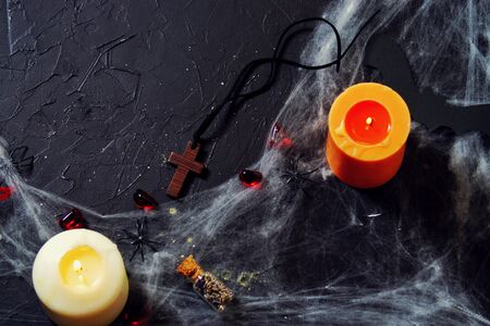 Halloween. burning candle on a web with spiders and bats on a black background.