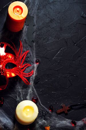Halloween. red female mask lies next to a burning candle on a web with spiders and bats on a black background. Banco de Imagens - 128259361