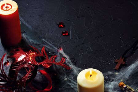 Halloween. red female mask lies next to a burning candle on a web with spiders and bats on a black background.