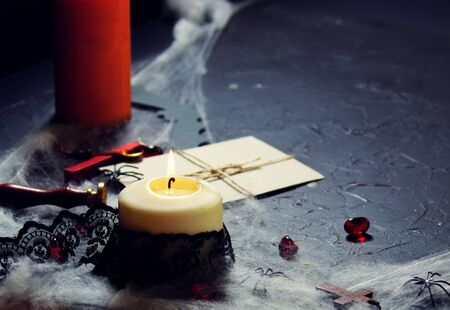 Masonic secrecy concept with a lit candle on a letter made of old vintage paper with red wax seal stamp against a black background with copy space.
