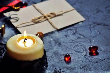 Concepto de secreto masónico con una vela encendida en una carta hecha de papel vintage antiguo con sello de cera roja sobre un fondo negro con espacio de copia.