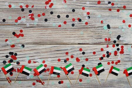 December 2 is the independence day of the United Arab Emirates. happy day of patriotism, faith, freedom. Mini flags on wooden background with confetti