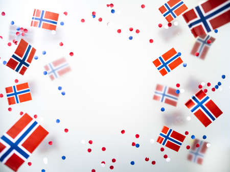 Norwegian independence day, Constitution day, may 17. holiday of freedom, victory and memory. concept of patriotism and faith. paper confetti and mini flags on white foggy background. High quality photo