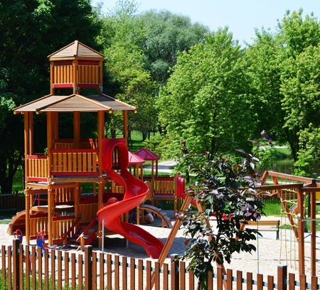 ensures: Wooden castle with slide on a modern playground, situated in a leisure park. The park is on the edge of a town and, with its woody, green, natural surroundings and various facilities, ensures relaxation and recreation for the town