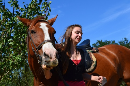 A young woman leading a brown horse at a horse farm. photo