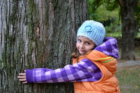 forest management: cute little girl smiling and hugging a tree