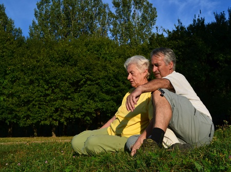 Retired couple sitting and relaxing on a glade on a beautiful sunny afternoon, with woods in the background. photo