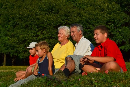 Senior couple and their grandchildren talking and relaxing in nature on a sunny afternoon, with trees in the background. photo