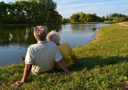 Ein älteres Paar, Sitzen und Relaxen zusammen auf einem See an einem sonnigen Nachmittag.