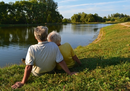 A senior couple sitting and relaxing together on a lakeside on a sunny afternoon. photo