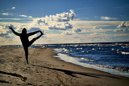 Yoga silhouette at sea cost and sunset Редакционное