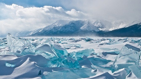 snow break: Winter Baikal, ice hummocks on a background of mountains Stock Photo