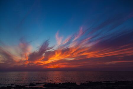flame like: Beautiful sunset on the Mediterranean sea in Cyprus. Rocky sea shore and flame-like clouds in the sky.